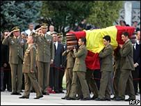Spanish King Juan Carlos (left) and son Prince Felipe (centre) salute as the bodies of 17 Spanish soldiers who died in a helicopter crash in Afghanistan arrive in Madrid