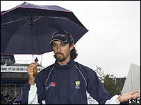 Australia's Jason Gillespie shelters from the rain