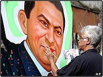 Egyptian man painting poster of incumbent Egyptian President Hosni Mubarak