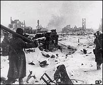Russian soviet troops trudge through the snow amid the ruins of Stalingrad, AP