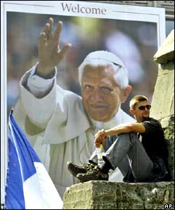 A pilgrim in front of a Pope Benedict XVI poster
