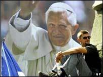 Man beneath Pope poster