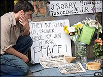 Un joven brasileño junto a los tributos puestos para Jean Charles de Menezes en la estación de Stockwell, donde fue muerto.