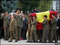 King Juan Carlos of Spain (left) salutes the coffin of a Spanish soldier killed in Afghanistan