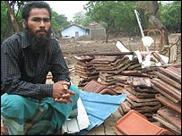 Diver J Najib beside his destroyed home