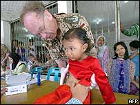 A German medical member treats a young girl at an Indonesian refugees' camp in Banda Aceh