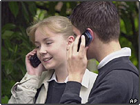 Two teenage children using mobile phones