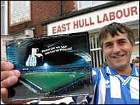 A Brighton fan with a small version of the postcard outside John Prescott's office