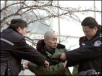 Chinese policemen restrain a Chinese protester, 06/01/2005