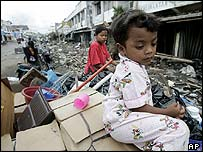 Acehnese girl waits as parents retrieve goods from their damaged shop