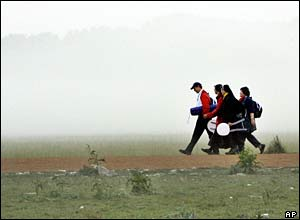 Catholic pilgrims walking through a misty field