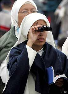 Nun looks through binoculars as she attends the Pope's open-air mass near Cologne