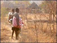 Villagers carry blankets and food