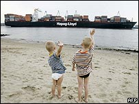 Two young boys wave at a Hapag-Lloyd container ship