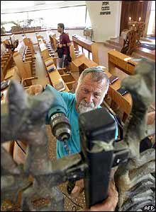 A worker dismantles the interior of the synagogue in Ganei Tal