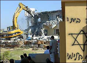 An Israeli bulldozer demolishes a house in Dugit