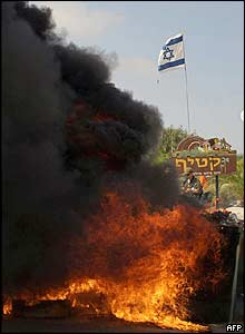 Debris is set on fire by Jewish settlers at the entrance to the Katif settlement to prevent the army from entering