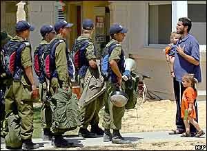 An Israeli settler pleads with an Israeli policeman in Atzmona