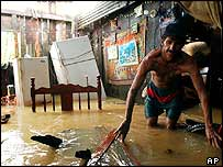 Luis Silva tries to salvage his belongings from his flooded home in Naranjal de Sarapiqui, Costa Rica, north-east of the capital San Jose