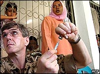 A German army medic prepares to vaccinate a child at an Indonesian refugees' camp in Banda Aceh, 11 January 2005.