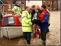 Rescue workers help residents out of the floods in Carlisle, UK