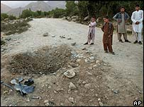 Afghan boys stand near a blast site on the outskirts of Kabul