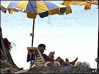 A tourist reads a book on a beach