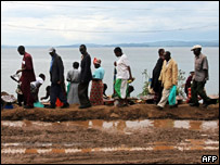 Congolese citizens walk along the coast of the Kivu River