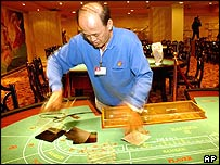 A worker at the new Greek Mythology Casino in Macau prepares a table in one of the casino's gambling halls, Wednesday, Dec. 22, 2004