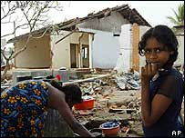 A Sri Lankan girl in front of her ruined house