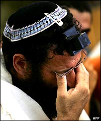 A Jewish settler cries as he prays during the last praying ceremony at the synagogue of the Gaza strip settlement of Netzarim
