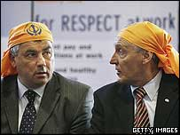 Union leaders Brendan Barber (L) of the Trades Union Congress and Tony Woodley of the Transport and General Workers Union wear head scarves as they meet with sacked airline catering workers in Southall