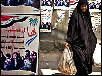Iraqi woman walks past a poster promoting women's rights in the new constitution