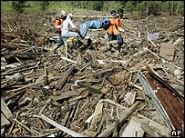 Volunteers carry a dead body out the debris in Banda Aceh, 13 January 2005