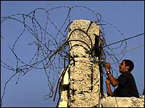 A West Bank settler fastens barbed wire to a wall