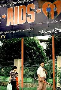 A Burmese family passes Saturday, Aug. 20, 2005 an anti-AIDS campaign board erected in downtown Rangoon.