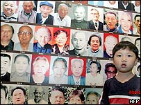 A Chinese boy stands by a display showing hundreds of photographs of survivors of the Nanjing massacre, at an exhibition in Beijing, 23 August 2005.