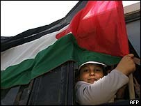A Palestinian boy waves a flag close to Netzarim settlement in Gaza