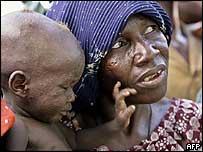 أم أفريقية وطفلها في انتظار المعونة الغذائية