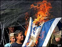 Youths burning an Israeli flag at Homesh
