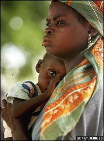 A woman waits outside a Save The Children centre with her son