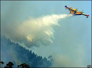 An Italian Canadair water-carrying plane drops its load over a fire near the Portuguese city of Coimbra