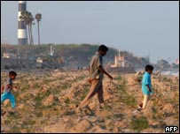 An Indian fisherman walks on the beach with his two sons following the tsunami