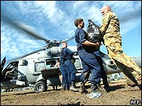 US soldiers make a chain to load relief goods into a Seahawk helicopter en route for a relief mission in the remote areas of the Aceh province at the military airport in Banda Aceh, 14 January 2005