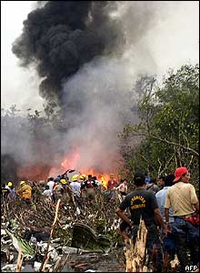Rescuers approach burning wreckage