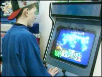 Child playing video game in arcade