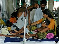 A boy lies on the lap of his mother in a hospital in Gorakhpur
