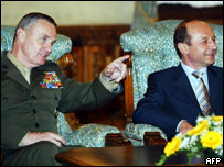 Romanian President Traian Basescu (R) listens to US General James Jones