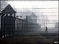 Auschwitz fence and figure in the distance