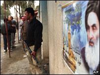 Un guardia vigila armado junto a un poster del clérigo chiita Ali al-Sistani, en Bagdad.